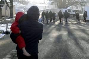 IMMIGRATION - MIGRANTS - REFUGIES POLITIQUES - REFUGIES DE GUERRE - REFUGIES ECONOMIQUES - SAARLAND - DEUTSCHLAND - SARRE - ALLEMAGNE. Lebach 20 janvier 2016. Une maman porte son enfant en combinaison d'hiver mais pieds nus dans le camp de réfugiés de Lebach, dans la banlieue de Sarrelouis et à 30 km au nord de Saarbrücken. Lebach accueille des réfugiés dans son camp depuis les années 50, il y en a encore 2000 aujourd'hui. PHOTO Alexandre MARCHI.