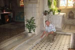 Paul Binse, voisin de l'église de Pulligny-sur-Madon, montre l'emplacement des fouilles effectuées pour retrouver la tombe des époux Jeanne et Robert des Armoises (DR)
