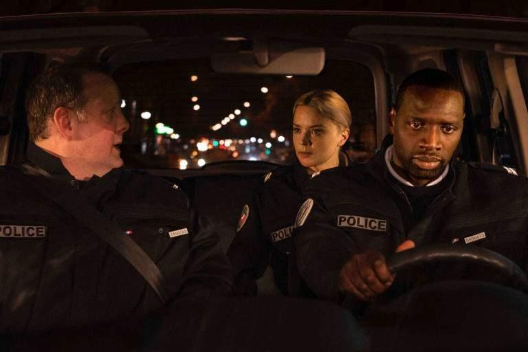 Trois policiers dans une voiture (joués par Grégory Gadebois, Virginie Efira et Omar Sy), dont on épie les regards les uns sur les autres.