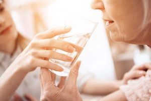 Un accompagnant aide une personne à boire de l'eau